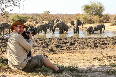 photographer sitting watching elephants at waterhole, Hwange NP